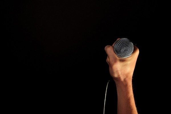 hand-with-microphone-on-black-background